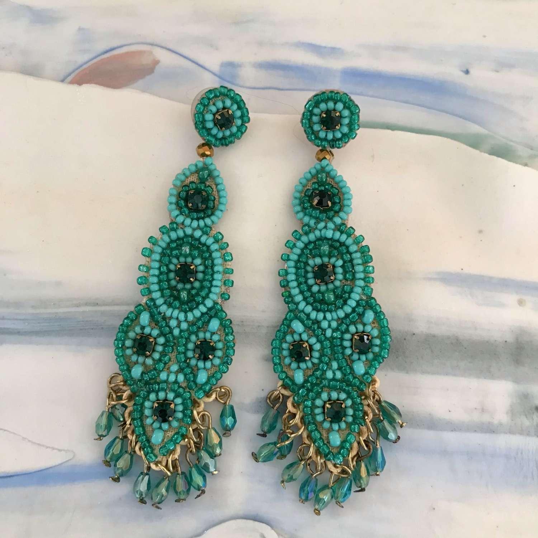 Long drop green statement earrings